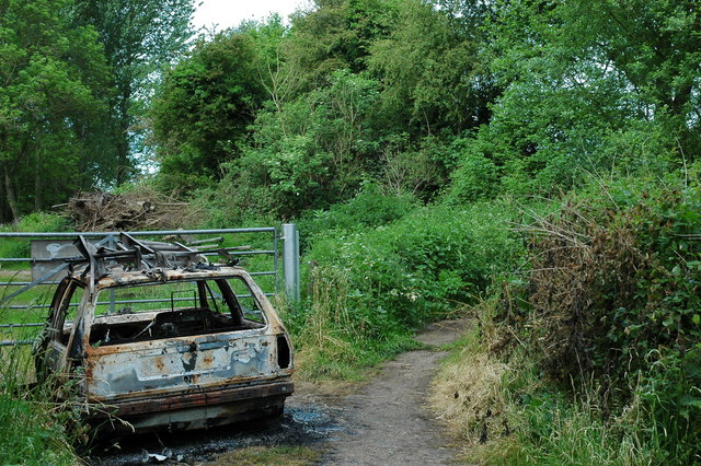 Burnt car at the footpath fork.