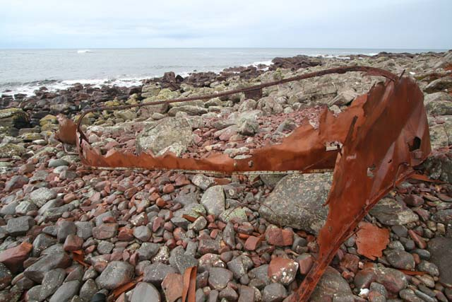 Rusty remains of boat on beach