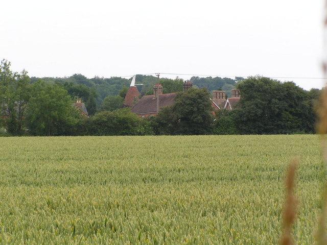 A view across an arable field to an Crockhurst Farm Oast , Tudeley.