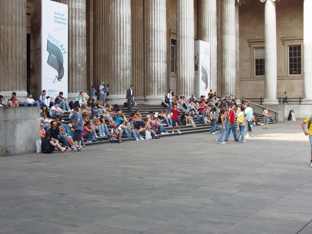 Visitors sit on the steps of the British Museum on a hot day