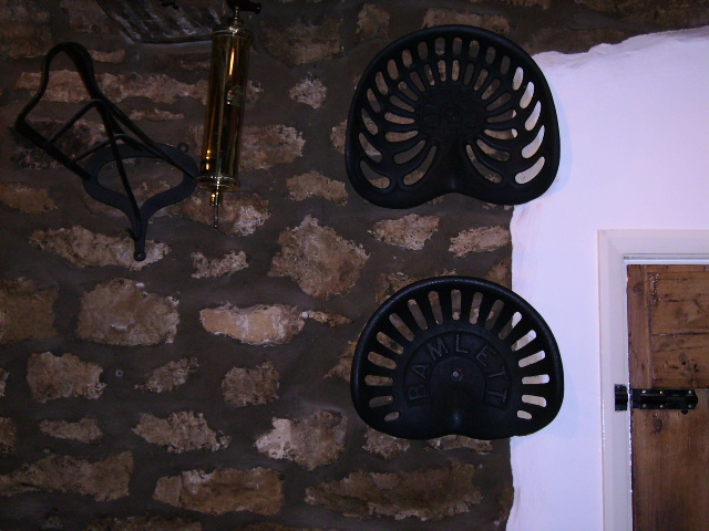 Restored tractor seats and farming implements in The Royal Oak Inn