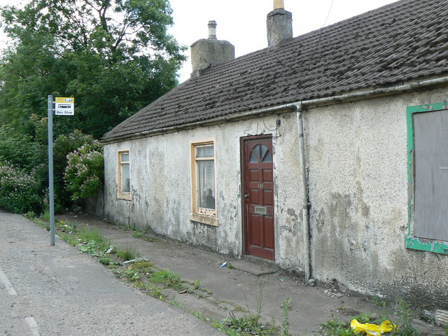 Abandoned cottage by the bus stop