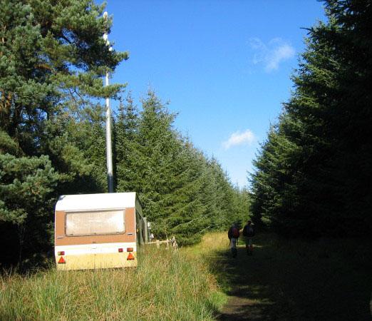 Mobile telephone mast and lone caravan.