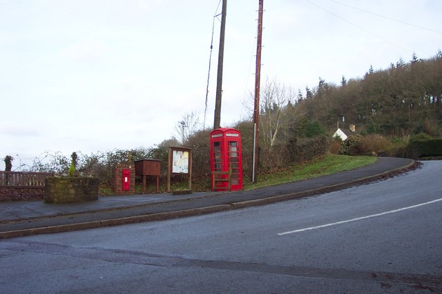 Postbox, notice board and phonebox by the B4293 at Itton Common.