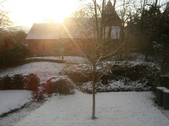 Folkington Church in winter with sun rising