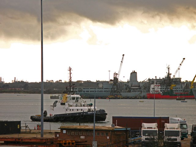 Troop ship under maintenance and tug