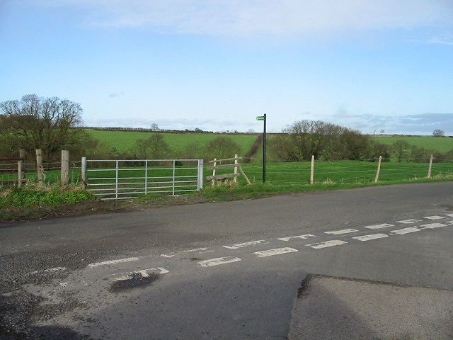 Road junction and footpath across farmland.