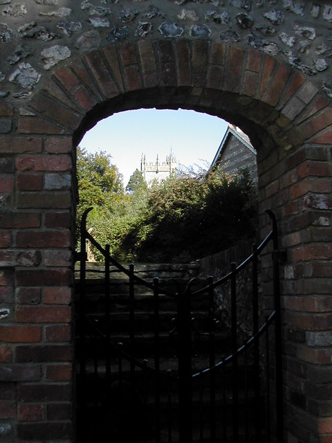 Piddletrenthide Church tower through an archway.