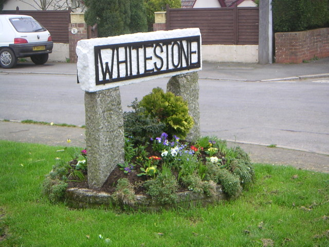 Whitestone Village sign with spring flowers