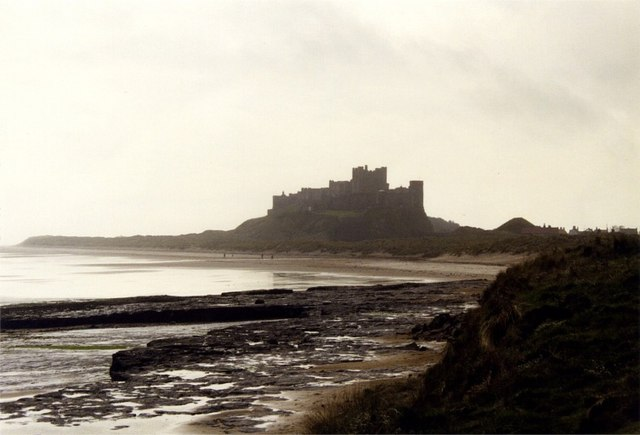Rocky bay at Harkess rocks with Bamburgh Castle silhouetted on horizon