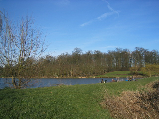 Fishermen on an artificial lake surrounded by attractive woodland