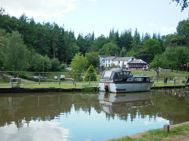 Motor launch on canal with visitor centre in the background