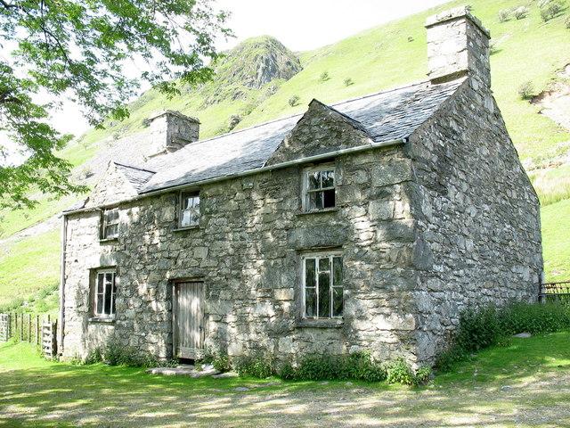 Sun-dappled facade of Allt-lwyd farmhouse