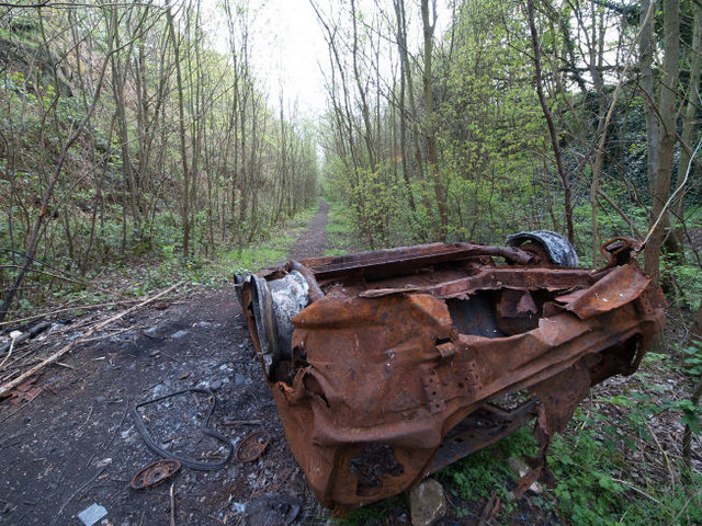 Burnt out car in railway cutting near site of former Darfield Station