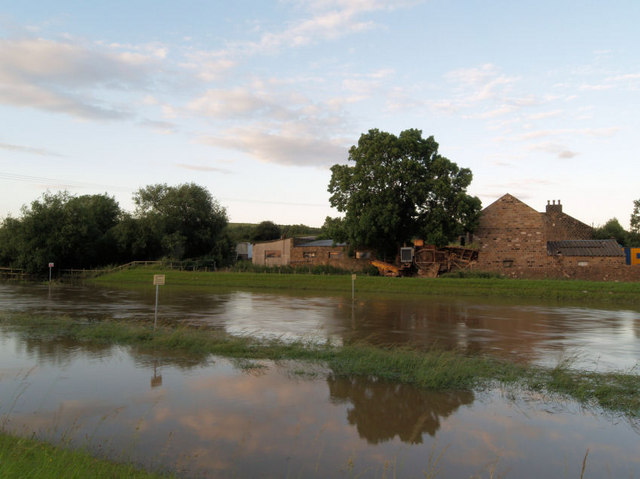 Flooded river Dearne with Little Houghton Millhouse in background