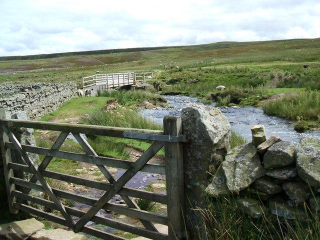 Bridge across swollen Deepdale Beck