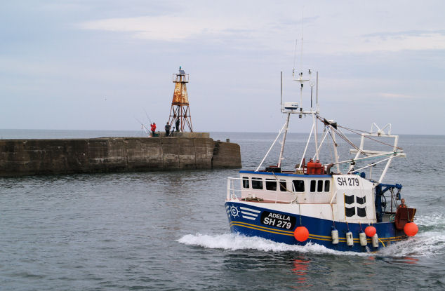 Amble north pier light with fishing boat.