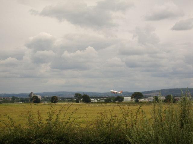 Plane taking off behind field near Inchinnan