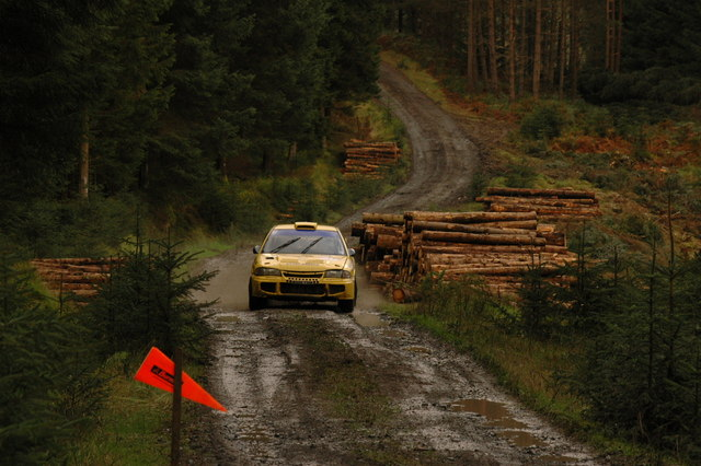 Rally car approaching a junction in the forest near Burnhead