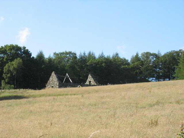 A roofless barn in a hay meadow