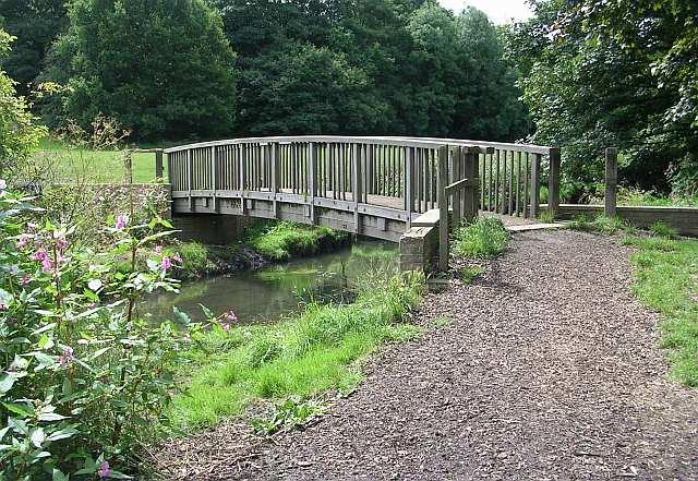 Wooden bridge over stream running through Springhead Park