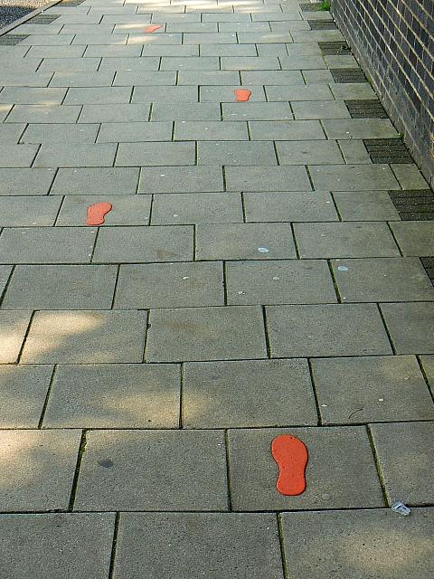 Orange footprints on the footpath, Princes Street, Swindon