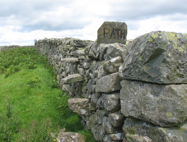 Old fashioned footpath stile in field wall