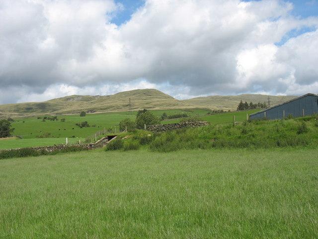 Isolated remnant of a railway embankment and an underbridge near the Tyddyn Felin farm buildings