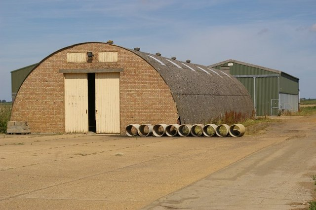 Nissen hut, with pipes arrayed alongside it