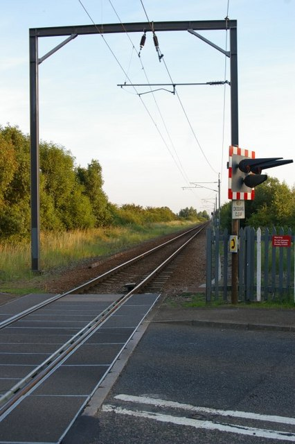 View down train tracks at level crossing