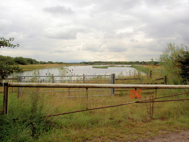 Gate in front of flooded gravel quarry.