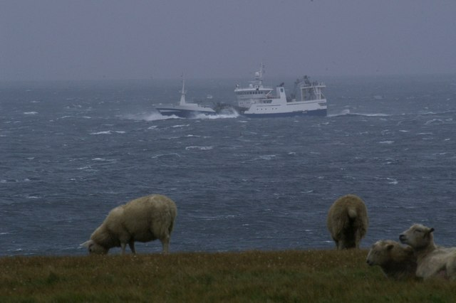 A fishing boat rounds Lamba Ness