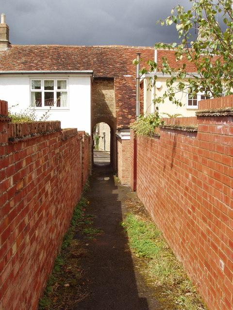 Footpath through archway between stone houses, Podington
