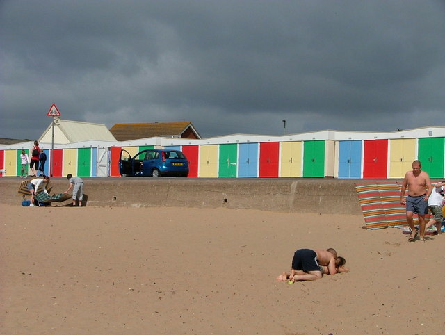 Colourful beach huts against a black sky
