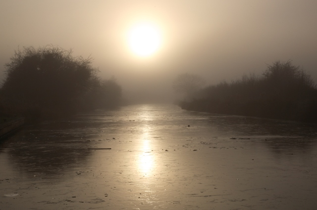 Frozen and misty canal