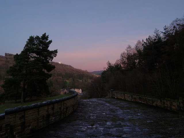 More Hall reservoir over spill weir with moon coming up over the trees