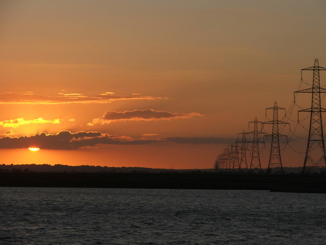 Pylons sweeping away from Dungeness towards the sunset