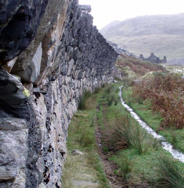 Curved stone wall protecting track