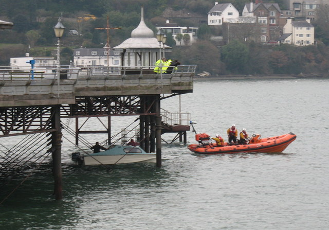 Recovered craft being towed out from under the pier