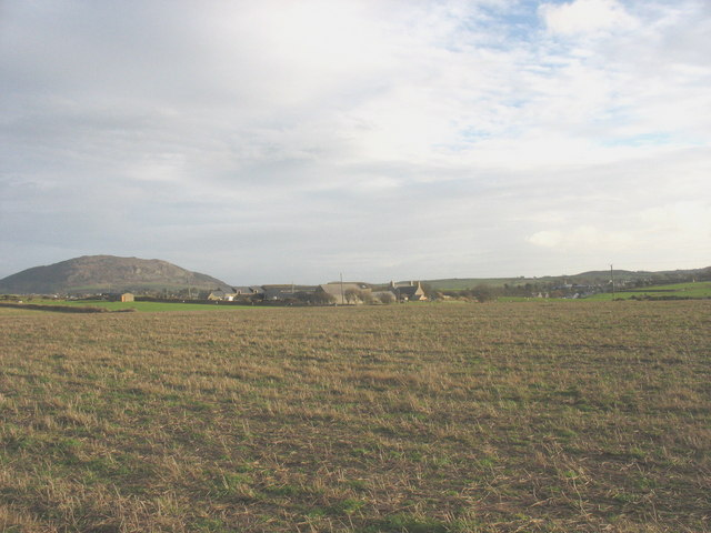 Farmhouse and outbuildings of Porth Dinllaen Farm viewed across a stubble field