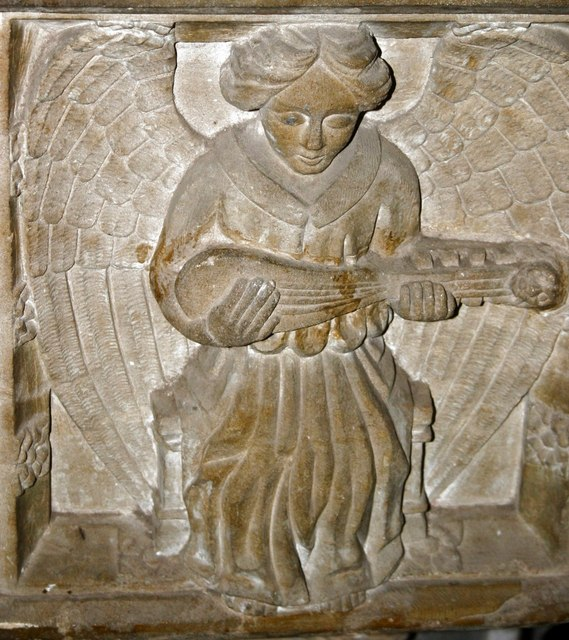 Carving of angel with musical instrument on font