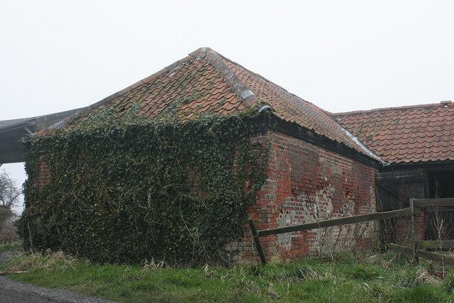 Red brick farm buildings beside footpath