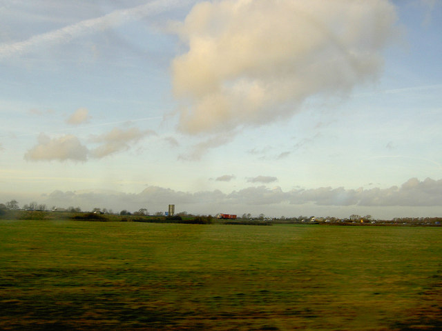 A distant M5 motorway crossing the Somerset Levels from the railway heading North to Bristol