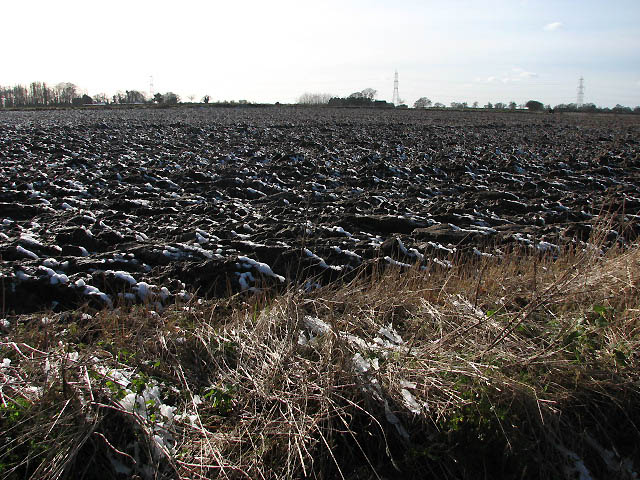 View across ploughed field with a sprinkling of snow