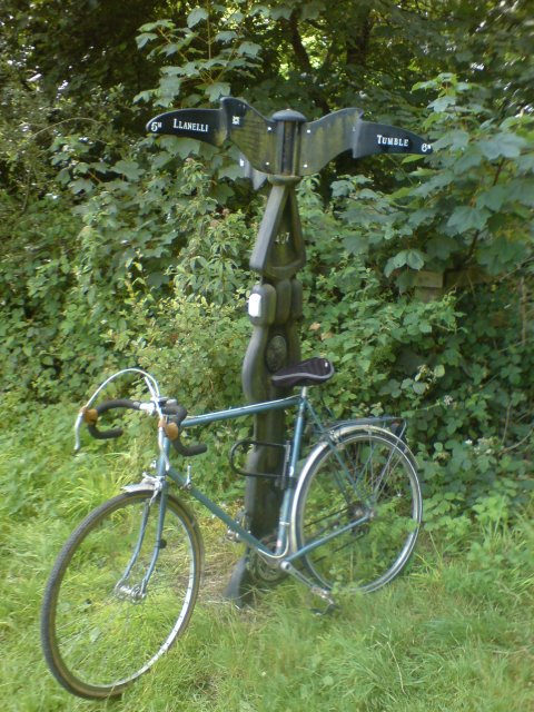 Bike leaning against cycle path mile post