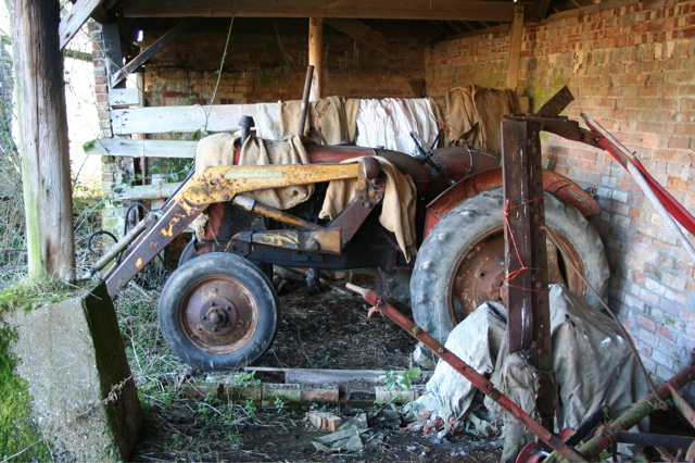 Retired tractor in derelict farm buildings