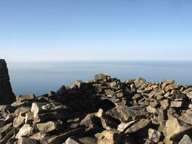 The wind shelter formed out of the hollowed-out cairn on the summit of the central peak of Yr Eifl