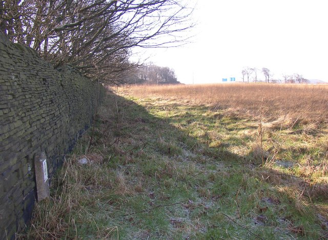 Looking along the old road boundary wall, New Hey Road, Fixby