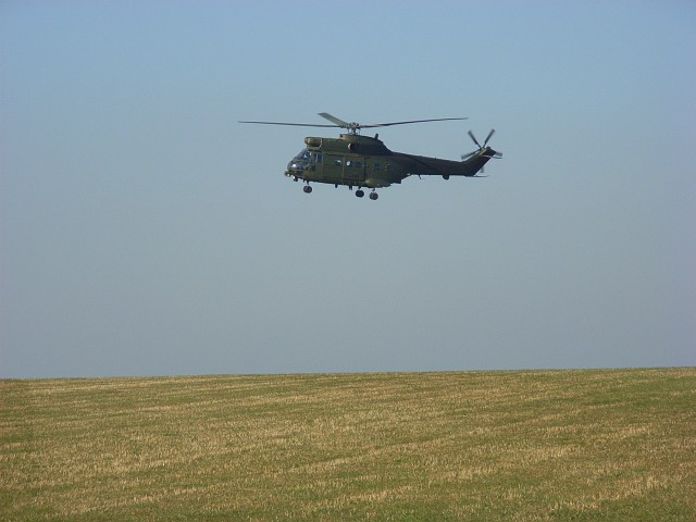 MOD helicopter being flown low over farmland above Shrewton