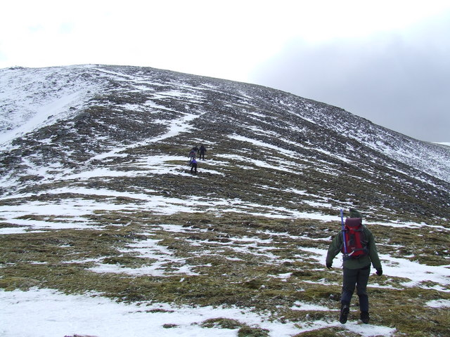 Walkers approaching the summit and battling the wind
